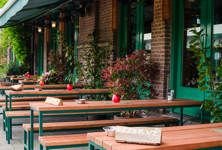 Bar in Oost, Amsterdam, Netherlands. Outside street view of long wooden tables with sign Reserve. Banco de Imagens