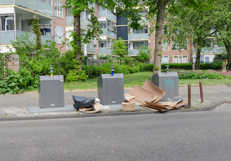 Amsterdam Oost. East side neighborhoods. View of three garbage containers for segregation with big carton near it. Street contamination. Copyspace.