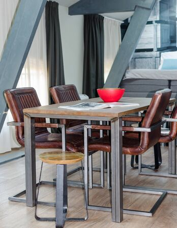 AMSTERDAM, NETHERLANDS - May 2019: Wood and metal dining table with cozy leather chairs, wooden floor in a mansard room with a rented apartment.