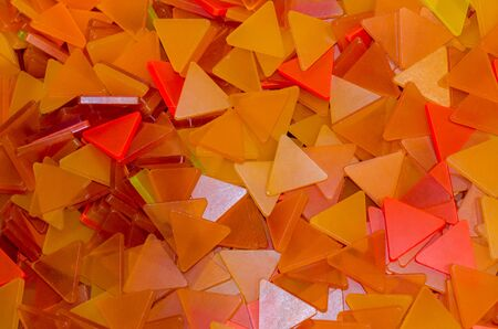 A lot of orange plastic triangles background. Orange and yellow triangles.