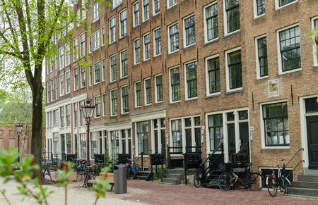 Amsterdam, Netherlands - May 03 2019. Street view of a long brick house with big windows and bicycles near the entrance.