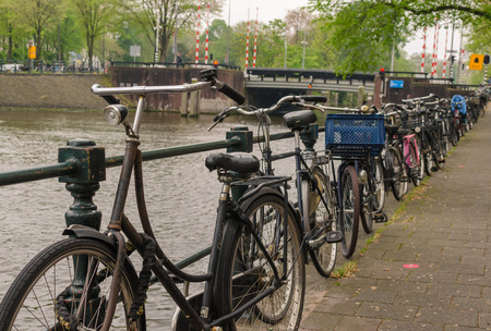 Amsterdam, Netherlands - May 03 2019: A lot of bicycles in line by river canal. Low point view. 新聞圖片