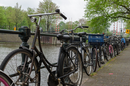 Amsterdam, Netherlands - May 03 2019: A lot of bicycles in line by river canal. Low point view. Redactioneel