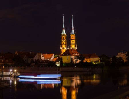 WROCLAW, POLAND - August 05, 2019: Night cityscape. Historical district Ostrow Tumski Poland with the spiers illuminated of the cathedral of St. John the Baptist ...