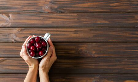 Woman hands with white cup with red cherries on dark wooden desk background. Flat lay. Top view. Backdrop. 版權商用圖片
