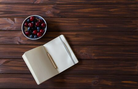 An small open notebook with pencil with bowl with cherries and blueberries on wooden desk background. Top view. Flat lay. Backdrop. 版權商用圖片