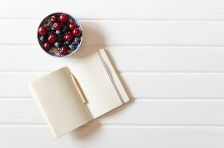 An small open notebook with pencil with bowl with cherries and blueberries on the white wooden desk background. Top view. Flat lay. Backdrop. 版權商用圖片