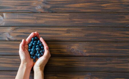 Woman hands with blueberries on dark wooden desk background. Flat lay. Top view. Backdrop. 版權商用圖片