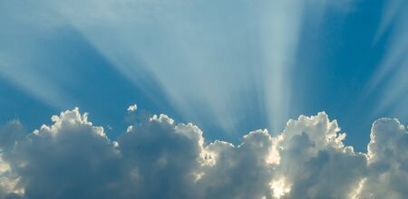 Optimistic sunset rays behind the clouds. Glow in the sky. Symbol of light. Beautiful scene of nature. 版權商用圖片
