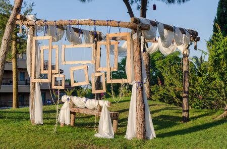 Rustic Wedding Photo booth Set-up outside. Wooden bench with hanging wooden frames as background.