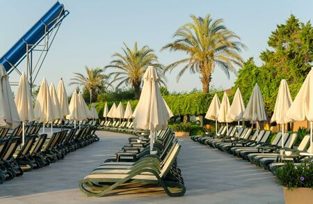 Rows of empty plastic sunbeds on the terrace near pool. Imagens