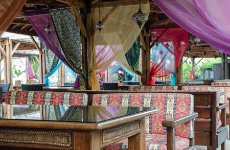 Turkish style design restaurant. Outside terrace with colorful seats, curtains and mosaic lamps. Selective focus