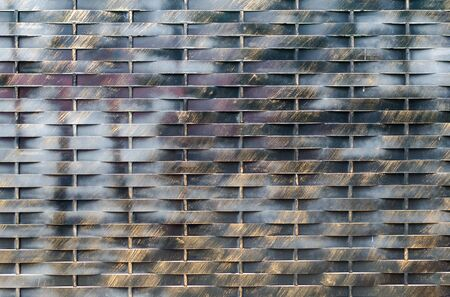 Old black and brown metal wall background. Horisontal and vertical lines gate. City or rural rtexture. Dark geometric wallpaper