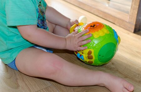 Child is playing with bright round plastic toy inside. Side view. 版權商用圖片