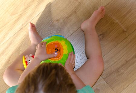 Child is playing with bright round plastic toy inside. top view.