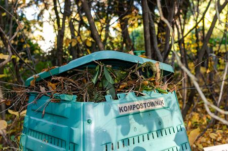 Full Outside plastic compost container with leaves and branches. Text on polish is Compost bin.