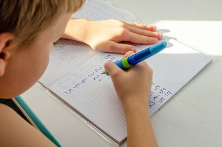 Kid hands doing math homework. Close up of young boy hand holding pen and writing a math homework close-up. concept of education at home. Banco de Imagens