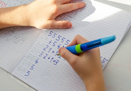 Kid hands doing math homework. Close up of young boy hand holding pen and writing a math homework close-up. concept of education at home. Imagens