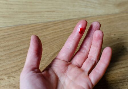 Finger with red blood drop caused by accident, knife cut.