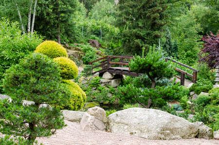 Japanese garden view with shaped trees, stones, sand, wooden bridge. Poland, Shklarska poreba. Selective focus.