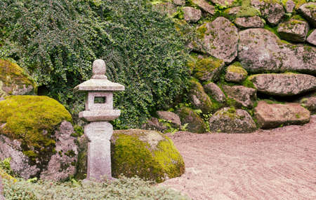 Old stone lantern in the Japanese garden. Poland, Shklarska poreba. Selective focus.