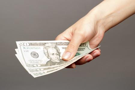 dolar: Mano femenina que sostiene un 20 Dolar en una oscura