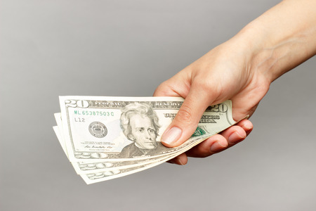 signo de pesos: Mano femenina que sostiene un 20 Dolar, sobre un fondo oscuro Foto de archivo