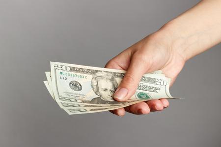 dolar: Female hand holding a 20 Dolar, on a dark background