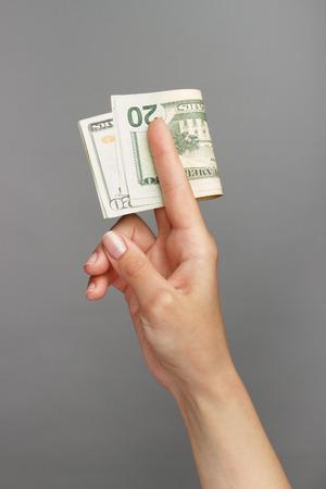 dolar: Mano femenina que sostiene un 20 Dolar, sobre un fondo oscuro Foto de archivo