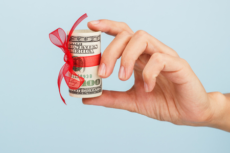 womans: womans hand is holding money on the blue background.. Dollar bills