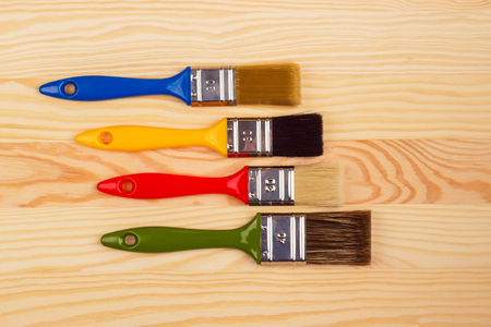 repairs: Four colored brushes for repairs on a wooden background, red, blue, green and yellow brush