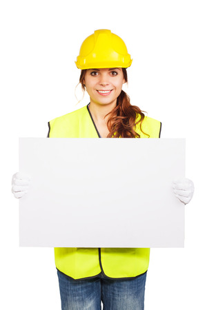 nameplate: Girl worker in a construction helmet and yellow vest holds nameplate in the hands, isolated Stock Photo