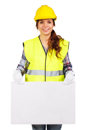 from below: Girl worker in a construction helmet and yellow vest holds nameplate from below, isolated