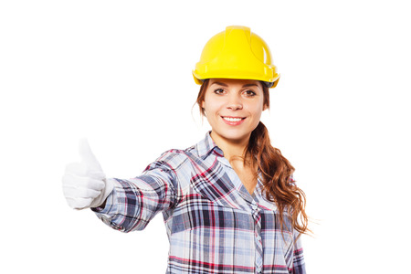 closed fist: Young smiling worker in the construction helmet shows thumb upwards from a closed fist, isolated Stock Photo