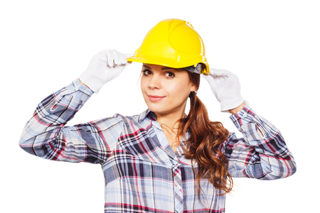 Portrait of young woman worker holds construction helmet by hands in white gloves, isolated