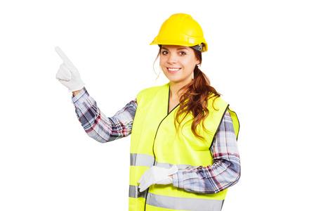 dedo indice: Trabajador de la muchacha en un casco de construcción y chaleco amarillo muestra el dedo índice hacia arriba, aislado Foto de archivo