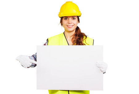 nameplate: Girl worker in a construction helmet and yellow vest shows by index finger on the nameplate, isolated
