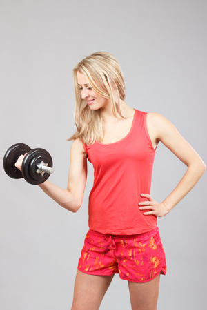 youthfulness: Sportswoman makes exercise with dumbbell on a gray backgrounf