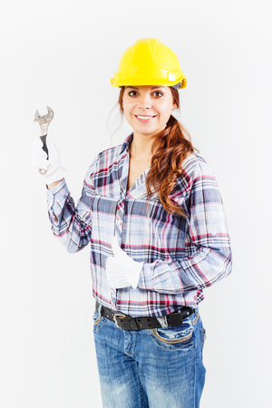 closed fist: Girl worker in a construction helmet holds wrench and shows thumb upwards from a closed fist