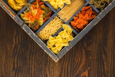 typesetter: Vintage wooden typesetter case with dividers including different types of pasta on the wooden background Stock Photo