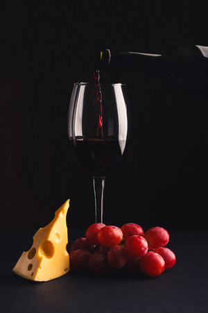 cabernet sauvignon: Glass with wine, a pice of cheese and bunch of grapes