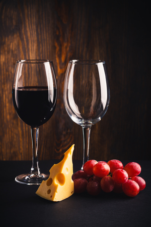 cabernet sauvignon: A glass with wine, an empty glass, a pice of cheese and bunch of grapes