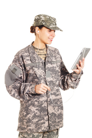 corporal: Young smiling girl-soldier in the camouflage military uniform holds tablet Stock Photo