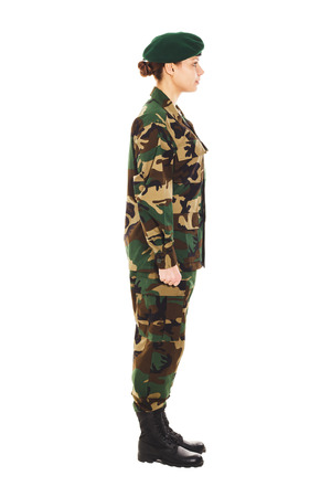 green beret: Soldier girl in the green camouflage military uniform and beret stands by the front