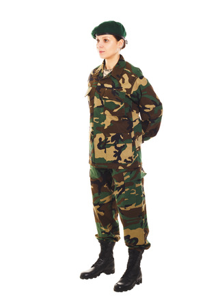 corporal: Soldier girl in the camouflage military uniform and beret stands by the front, hands behind the back Stock Photo