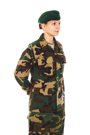 green beret: Soldier girl in the green camouflage military uniform and beret stands by the front, hands behind the back