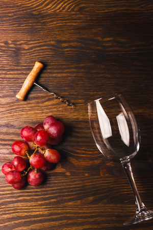 cabernet sauvignon: Empty glass for wine, corkscrew and bunch of red grapes