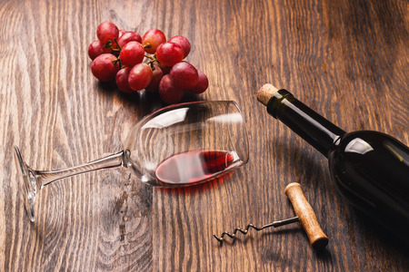 cabernet sauvignon: Glass with red wine, corkscrew and bunch of red grapes