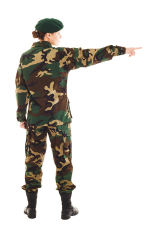 green beret: Soldier girl in the camouflage military uniform and beret shows an index finger to the right side, isolated