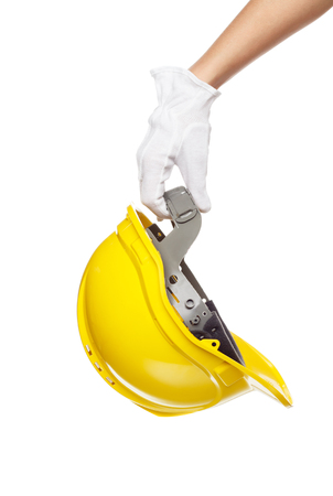 architect tools: Yellow construction helmet in the hand, isolated